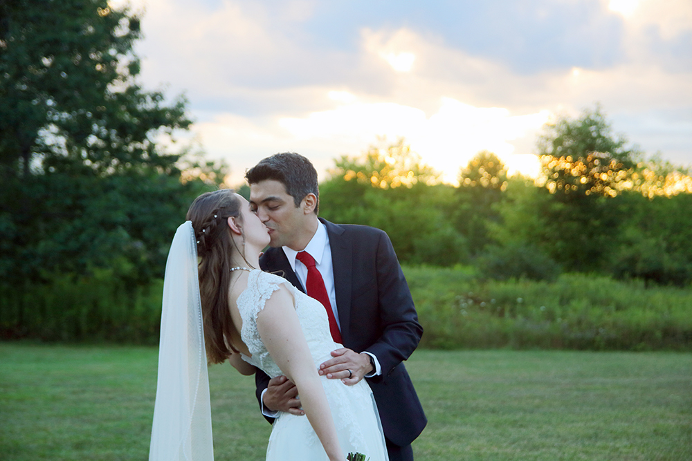 Newly married couple kissing in front of a sunset at their reception