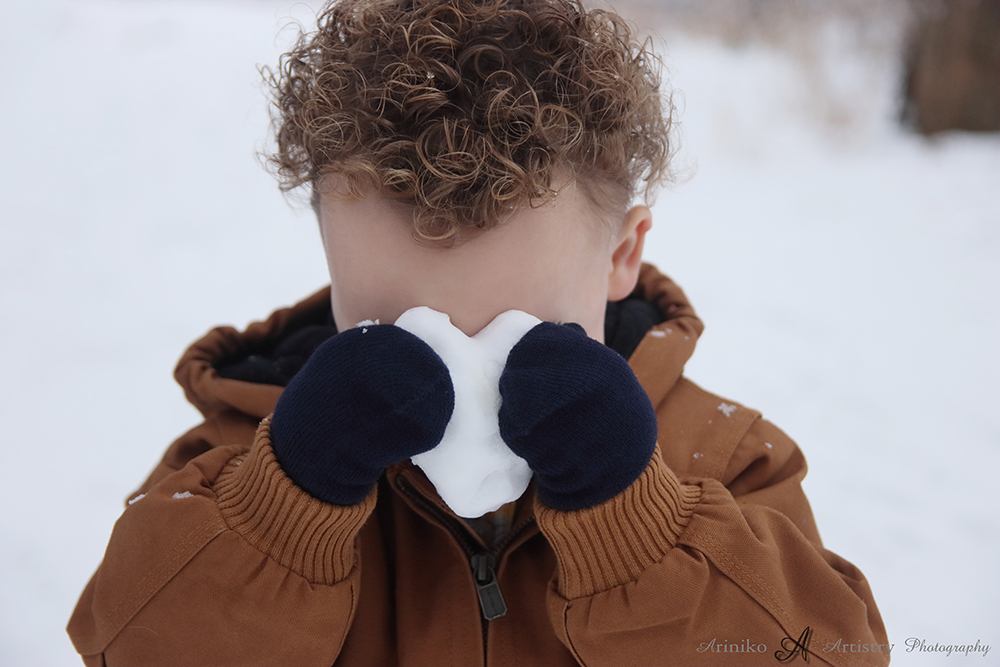 Soon to be brother hiding behind little snow heart during maternity session at Harris Nature Center in Okemos, Michigan